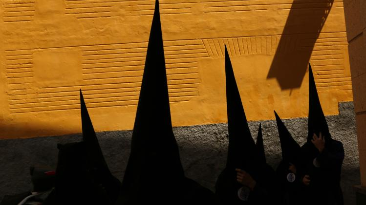 Penitents of San Bernardo brotherhood make their way to church before taking part in procession during Holy Week in Andalusian capital of Seville