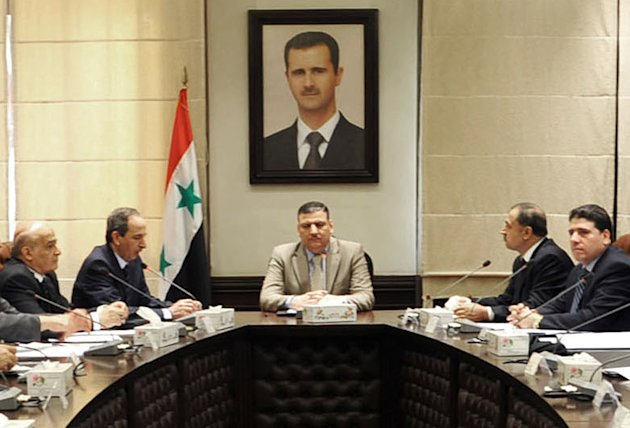 In this undated photo released by the Syrian official news agency SANA on Sunday, Aug. 5, 2012, Syrian Prime Minister Riad Hijab, center, speaks under the portrait of the Syrian President Bashar Assad during a meeting in Damascus, Syria. Hijab defected and fled to neighboring Jordan, a Jordanian official and a rebel spokesman said Monday, Aug. 6, 2012. (AP Photo/SANA)