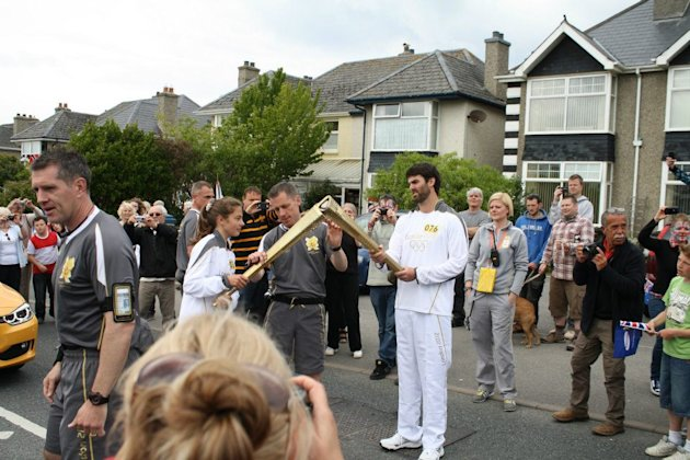 "Tommy Gee ""kisses"" the next Torch in the Olympic Torch Relay run in Newquay"