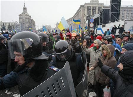 Interior Ministry personnel leave Independence Square as pro-European integration protesters gesture in Kiev