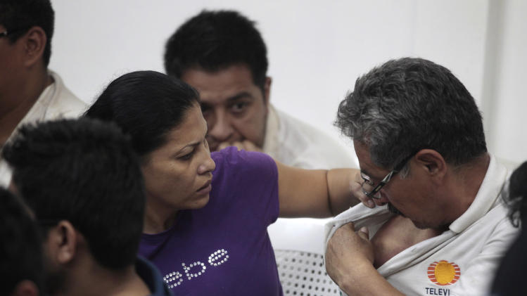 Mexican national Raquel Alatorre Correa, left, looks at the shoulder of a fellow detainee, both facing organized crime and money laundering charges, during a court hearing to face additional indictments, in Managua, Nicaragua, Friday, Aug. 31, 2012. Costa Rican authorities say Alatorre is believed to be the leader of a group posing as Televisa journalists transporting millions of dollars to Costa Rica to pay for a load of drugs that had been smuggled into the United States. The Aug. 20 seizure has pulled back the curtain on Nicaragua's role as a conduit between South American cocaine producers and the Mexican drug cartels that move their product into the United States. (AP Photo/Esteban Felix)