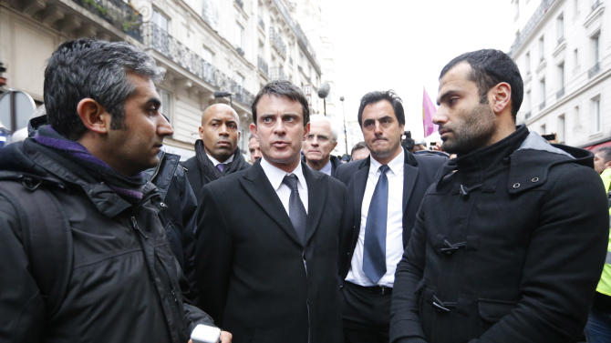 French Interior Minister Manuel Valls, center, talks with unidentified Kurdish activists after visiting the scene where three Kurdish women were shot dead, in Paris, Thursday, Jan. 10, 2013. Police say three Kurdish women have been shot dead at a pro-Kurdish centre in Paris in what the French interior minister is calling an execution. (AP Photo/Jacques Brinon)