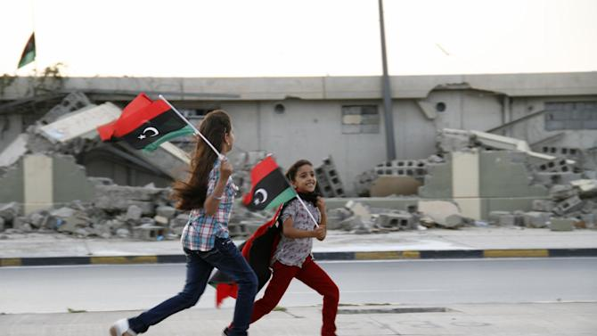 In this Tuesday, Oct. 23, 2012 photo, two Libyan girls run with national flags in front of the destroyed remnants of deposed leader Moammar Gadhafi's once feared Bab al-Aziziyah compound on the anniversary of his fall in Tripoli, Libya. One year on the country is still trying to overcome the legacy of one of the most erratic leaders of modern times as well as a brutal eight month struggle that left the country awash in weapons, militias and very few viable institutions of the state. (AP/Paul Schemm)