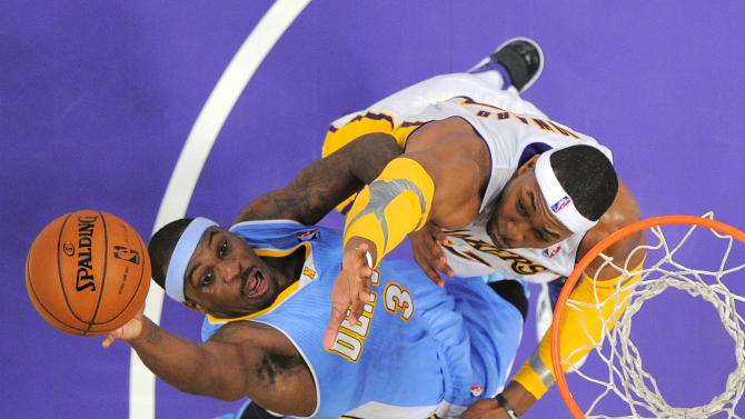 Denver Nuggets guard Ty Lawson, left, goes up for a shot as Los Angeles Lakers center Dwight Howard defends during the first half of their NBA basketball game, Sunday, Jan. 6, 2013, in Los Angeles.  (AP Photo/Mark J. Terrill)