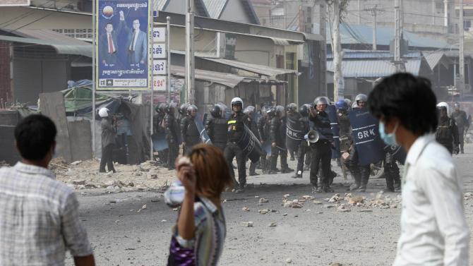 A worker throws a stone after clashes broke out during a protest in Phnom Penh