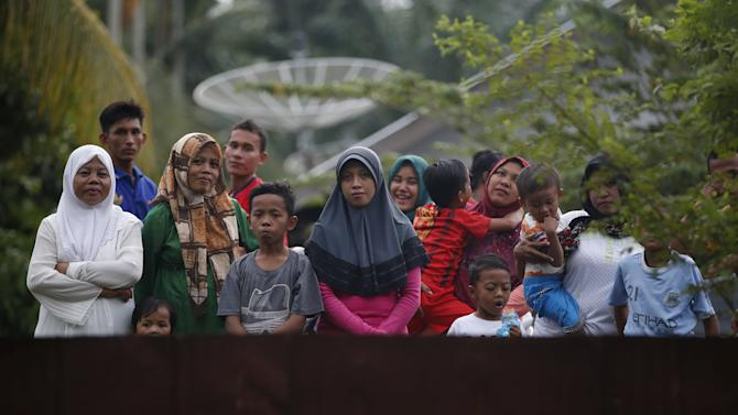 Local residents look over a fence at a camp housing Rohingya and Bangladeshi migrants, who arrived in Indonesia last week by boat, in Aceh Timur regency near Langsa in Indonesia's Aceh Province