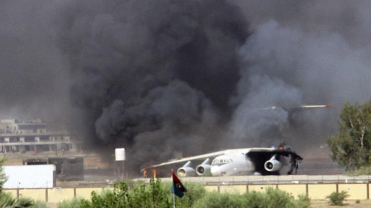 In this Saturday, July 26, 2014 frame grab from video obtained from a freelance journalist traveling with the Misarata brigade, shows an airplane on the tarmac of the airport belching black smoke into the air during fighting between the Islamist Misarata brigade and a powerful rival militia, in Tripoli, Libya. The battle for control of Tripoli's international airport began two weeks ago when Islamist-led militias - mostly from the western city of Misrata - launched a surprise assault on the airport, under control of rival militias from the western mountain town of Zintan. Heavy clashes in the country's restive east between Libyan soldiers loyal to a renegade general and Islamist-led militias killed dozens of people including civilians, health officials said Sunday. On Saturday, the U.S. evacuated its diplomats in Tripoli to neighboring Tunisia and shut its embassy. (AP Photo/AP video)