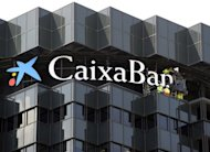 "Workers unveil the new logo of the ""CaixaBank"", Spain's third largest bank, on June 30, 2011 in Barcelona. Spain's top four banks will build a new 11.3-billion-euro ($15 billion) cushion against bad loans, latest statements showed Monday, but investors feared it was not enough"