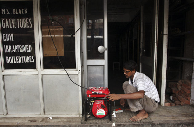 An Indian shopkeeper fixes an electric generator at his shop in New Delhi, India, Tuesday, July 31, 2012. India's energy crisis cascaded over half the country Tuesday when three of its regional grids 