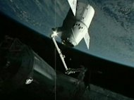 This frame grab from a NASA video shows the robotic arm of the ISS grappling SpaceX&#39;s Dragon capsule on May 25. The station&#39;s robotic arm, which grabbed the capsule on its approach May 22, has already been re-grappled to the Dragon, she said