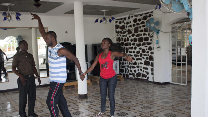 """In this Aug. 3, 2012 photo, professional dancer Georges Exantus, left, teaches a member of a professional dance group as they prepare for a concert in Port-au-Prince, Haiti. Exantus thought he'd never dance again. The earthquake three years ago in Haiti's capital flattened the apartment where he was living, where he spent three days trapped under a heap of jagged rubble. After friends dug him out, doctors amputated his right leg just below the knee. Israeli doctors and physical therapists who came to Haiti after the quake sent him to Israel for surgery and rehabilitation. Three years later, the 32-year-old professional dancer is back on the floor, spinning away as he does the salsa, cha-cha and samba. A prosthetic leg doesn't hold him back. """"As long as I'm living,"""" Exantus says, """"I'm going to dance."""" (AP Photo/Dieu Nalio Chery)"""