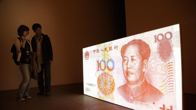 "In this photo taken Thursday, April 8, 2010, visitors look at the art work by American artist Tony Oursler entitled ""100 Yuan (People's Republic of China)"" which features a projection of a Chinese renminbi note with a talking Mao Zedong at a gallery in Beijing, China. China's yuan has joined the ranks of the most traded currencies for the first time, underlining the growing might of the world's second-largest economy. The yuan became one of the top 10 traded currencies in 2013, rising to No. 9 on the list due to a ""significant expansion"" in offshore trading, the Bank for International Settlements said in a report Thursday, Sep 5, 2013. (AP Photo/Ng Han Guan)"