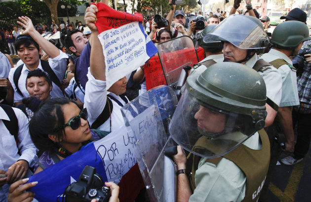 High school students shout at riot police during the year's first student protest in Santiago, Chile, Thursday March 15, 2012. High school students are protesting for further educational reforms, saying their demands were not met after seven months of protesting in 2011. (AP Photo/Roberto Candia)