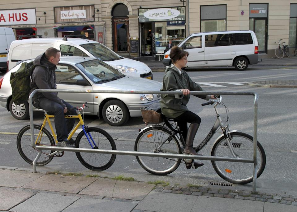 Two cyclists use a foot rest with handles at a major intersection on Oct.3, 2012. The photo is not from the route labeled a superhighway, but a downtown Copenhagen street with the same kind of bicycle-friendly features. (AP Photo/Jan M. Olsen)