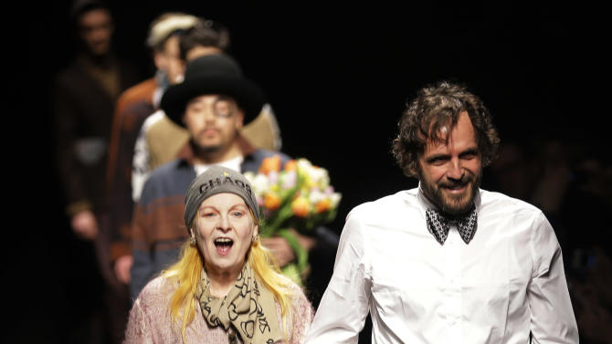 British fashion designer Vivienne Westwood is flanked by husband Andreas Kronthaler on the catwalk after presenting the Vivienne Westwood men's Fall-Winter 2013-14 collection, part of the Milan Fashion Week, unveiled in Milan, Italy, Sunday, Jan. 13, 2013. (AP Photo/Luca Bruno)