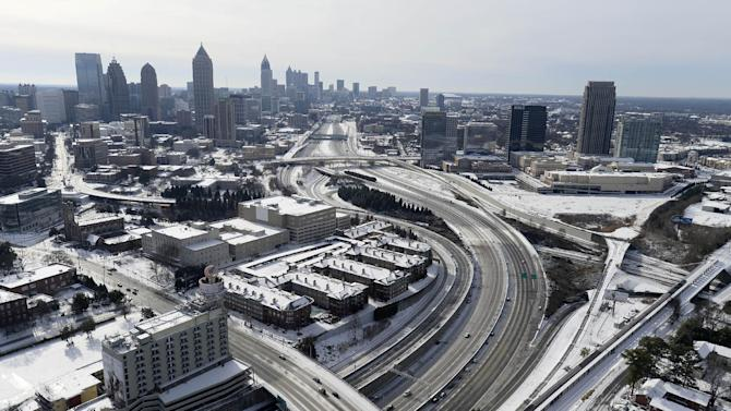 In this aerial view looking south toward downtown Atlanta, the ice-covered interstate system shows the remnants of a winter snow storm Wednesday, Jan. 29, 2014, in Atlanta. While such amounts of accumulation barely quality as a storm in the north, it was enough to paralyze the Deep South. (AP Photo/David Tulis)