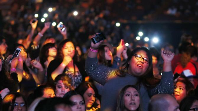 Spectators dance as they wait for the first-ever iHeartRadio Fiesta Latina to begin at The Forum in Inglewood, California