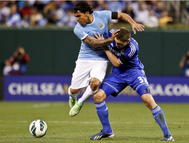 Manchester City's Carlos Tevez fights for the ball with Chelsea's Andreas Christensen during their friendly soccer match in St. Louis