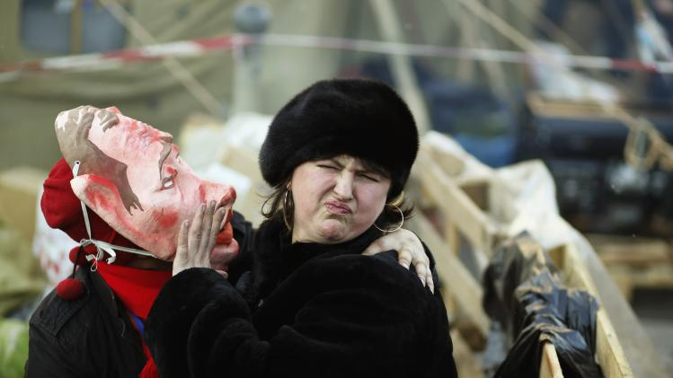 A pro-European integration protester wearing mask depicting Russian President Putin tries to kiss a woman during a rally in Independence square in Kiev