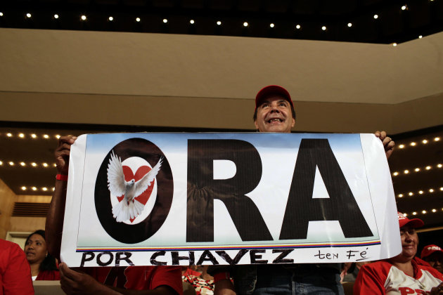 "A supporter of Venezuela's President Hugo Chavez holds up a sign that reads in Spanish ""Pray for Chavez"" during an event event honoring Venezuela's President Hugo Chavez at the Teresa Carreno theater"
