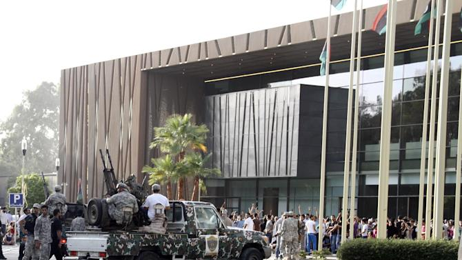 In this Sunday, Oct. 21, 2012 photo, Libyan army vehicles converge on protesters in front of of parliament, firing their heavy machine guns in the air in an attempt to disperse them in Tripoli, Libya. One year on, the country is still trying to overcome the legacy of one of the most erratic leaders of modern times as well as a brutal eight month struggle that left the country awash in weapons, militias and very few viable institutions of the state. (AP/Paul Schemm)