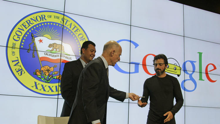 California Gov. Edmund G Brown Jr., center, hands his pen to Google co-founder Sergey Brin, right, after a bill signing for driverless cars at Google headquarters as state Senator Alex Padilla, left, looks on in Mountain View, Calif., Tuesday, Sept. 25, 2012.  The legislation will open the way for driverless cars in the state. Google, which has been developing autonomous car technology and lobbying for the legislation has a fleet of driverless cars that has logged more than 300,000 miles (482,780 kilometers) of self-driving on California roads. (AP Photo/Eric Risberg)