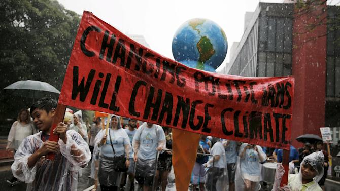 Indigenous boys hold a banner during a rally held the day before the start of the Paris Climate Change Conference (COP21), in Sao Paulo