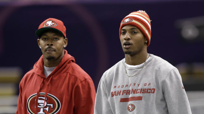 San Francisco 49ers cornerbacks Chris Culliver, right, and Carlos Rogers, left, walk onto the field for practice in the Superdome on Saturday, Feb. 2, 2013, in New Orleans. The 49ers are scheduled to play the Baltimore Ravens in the NFL Super Bowl XLVII football game on Feb. 3. (AP Photo/Mark Humphrey)