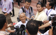 Khmer Rouge genocide survivor Bou Meng, center left, is surrounded by journalists outside the court of the U.N.-backed war crimes tribunal, on the outskirts of Phnom Penh, Cambodia, Thursday, June 30, 2011. The tribunal on Thursday held its fourth day trial on top four surviving members of the Khmer Rouge regime, blamed for the deaths of an estimated 1.7 million Cambodians in the 1970s. (AP Photo/Heng Sinith)