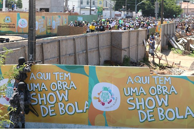 Riot police, bottom left, take position behind a wall, covered by a sign that promotes construction in progress, as protesters gather near the Castelao stadium in Fortaleza, Brazil, Wednesday, June 19