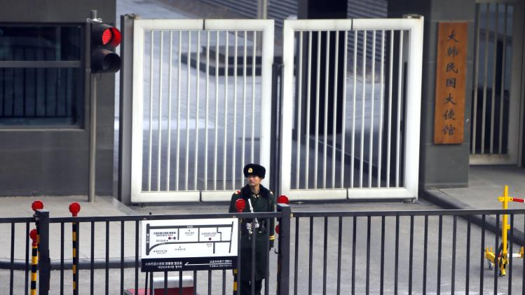 A paramilitary police official stands guard behind a gate at the South Korea embassy in Beijing