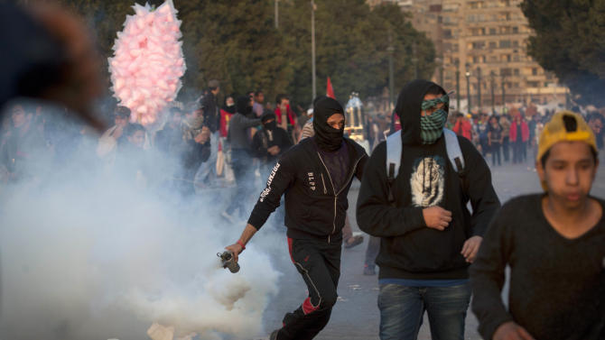 An Egyptian protester runs with a teargas canister during clashes with riot police in downtown Cairo, Egypt, Saturday, March 9, 2013. Security officials say a protester has died during clashes between police and hundreds of stone-throwing demonstrators in central Cairo. The officials say the protester died Saturday on a Nile-side road where clashes have been taking place daily between anti-government protesters and police near two luxury hotels and the U.S. and British embassies. (AP Photo/Nasser Nasser)