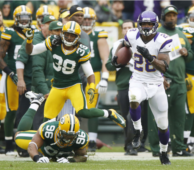 Minnesota Vikings running back Adrian Peterson breaks away from Green Bay Packers' Tramon Williams (38) and Mike Neal (96) for an 82-yard touchdown run during the first half of an NFL football game Su