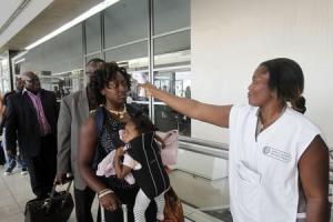 A health worker takes a passenger's temperature with an infrared digital laser thermometer at the Felix Houphouet Boigny international airport in Abidjan