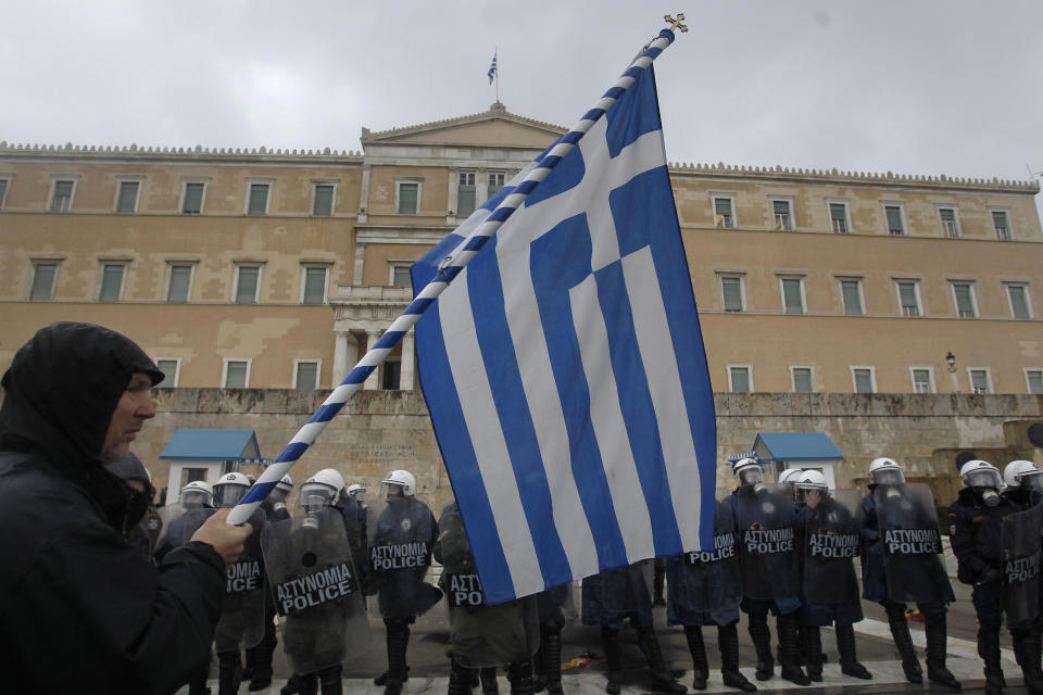 A protester holds a Greek flag outside the Greek Parliament during a 24-hour strike on Tuesday, Feb. 7, 2012. A general strike against the impending cutbacks  stopped train and ferry services nationwide, while many schools and banks were closed and state hospitals worked on skeleton staff. (AP Photo/Petros Giannakouris)