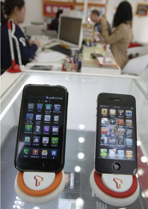 FILE - In this April 19, 2011 file photo, Samsung Electronics' Galaxy S, left, and Apple's iPhone 4 are displayed at a mobile phone shop in Seoul, South Korea. Two tech titans are squaring off in fede