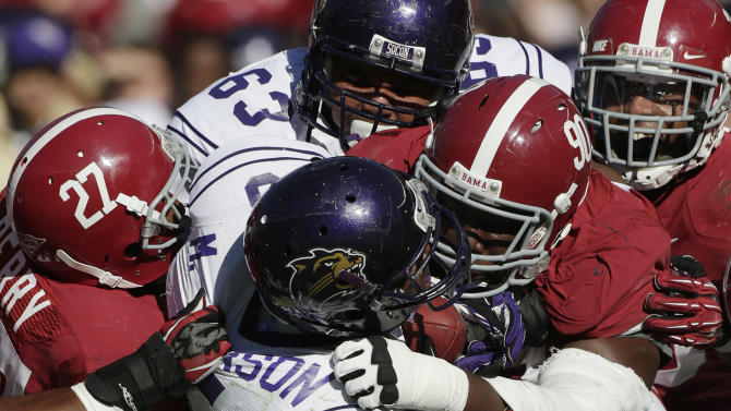 Western Carolina running back Michael Johnson (5) is stopped by the Alabama defense during the second half of an NCAA college football game at Bryant-Denny Stadium in Tuscaloosa, Ala., Saturday, Nov. 17, 2012. Defending for Alabama is defensive back Nick Perry (27), defensive lineman Quinton Dial (90) and  linebacker Nico Johnson (35). At rear is Western Carolina offensive lineman Matt DeGraffinreed (63). Alabama won 49-0. (AP Photo/Dave Martin)