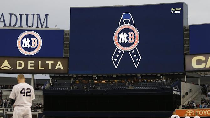 New York Yankees players observe a moment of silence in memory of the victims of the Boston Marathon explosions before a baseball game against the Arizona Diamondbacks at Yankee Stadium in New York, Tuesday, April 16, 2013. In big ways and small, New York is putting aside its heated and historical rivalry with Boston in a show of support after the Boston Marathon explosions.  (AP Photo/Kathy Willens)