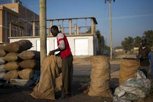A man fills sacks of charcoal for sale on the roadside …