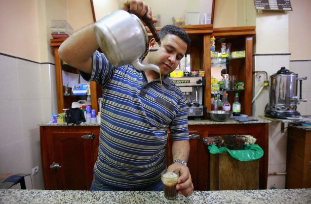 Sofiane Moussaoui, a 26 year-old waiter, poses for a picture as he serves tea for customers in a cafe in Algiers