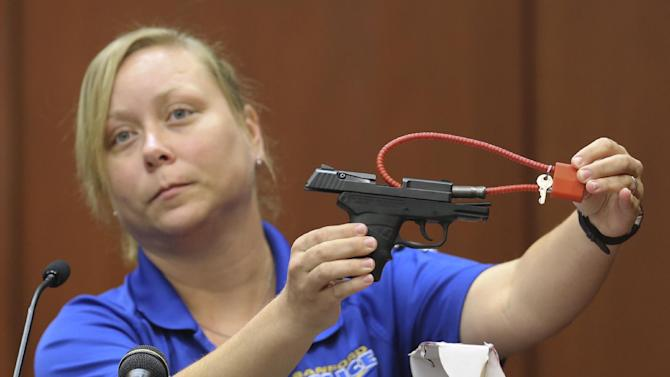Diana Smith, crime scene technician for the Sanford Police Department, shows the jury George Zimmerman's gun, which was collected as evidence at the crime scene, during Zimmerman's trial in Seminole circuit court in Sanford, Fla. Tuesday, June 25, 2013. Zimmerman has been charged with second-degree murder for the 2012 shooting death of Trayvon Martin.(AP Photo/Orlando Sentinel, Gary W. Green, Pool)