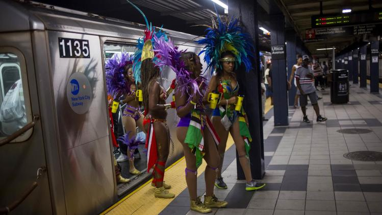 Participants walk out of a train as they arrive for the West Indian Day Parade in the Brooklyn borough of New York