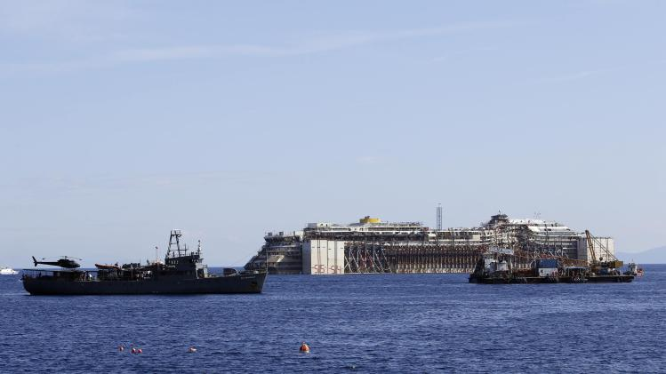 A military vessel patrols around the cruise liner Costa Concordia during the refloat operation maneuvers at Giglio Island