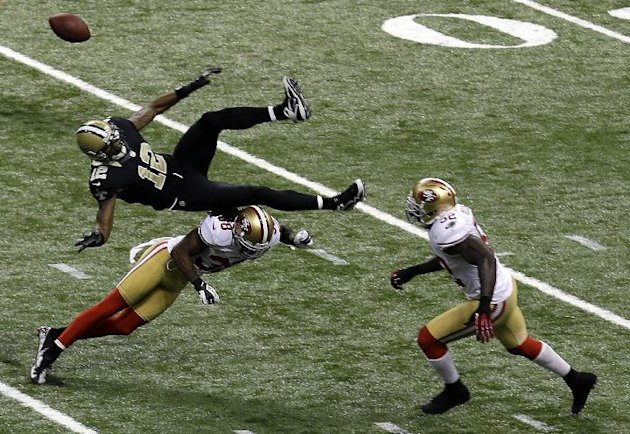 New Orleans Saints wide receiver Marques Colston (12) is upended by San Francisco 49ers strong safety Donte Whitner (31), causing an interception returned for a touchdown, in the second half of an NFL