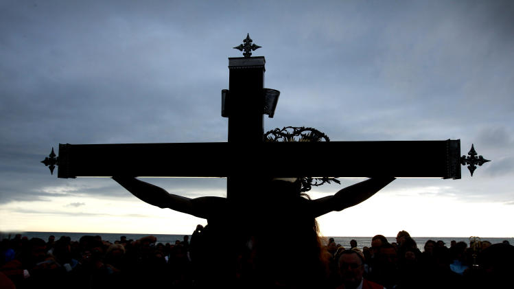Worshippers surround the icon of the Santisimo Cristo del Salvador brotherhood during a Holy Week procession in Valencia, in the early hours of Friday, April, 6, 2012. Hundreds of processions take place throughout Spain during the Easter Holy Week. (AP Photo/Alberto Saiz)