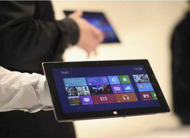 Microsoft representatives hold a new Surface tablet computer as it is unveiled by Microsoft in Los Angeles