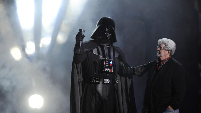 """FILE - In this Oct. 15, 2011 file photo, """"Darth Vader"""" accepts the Ultimate Villain award from """"Star Wars"""" creator George Lucas during the 2011 Scream Awards, in Los Angeles. A decade after George Lucas said """"Star Wars"""" was finished on the big screen, a new trilogy is destined for theaters after The Walt Disney Co. announced Tuesday, Oct. 30, 2012, that it was buying Lucasfilm Ltd. for $4.05 billion.  (AP Photo/Chris Pizzello, File)"""
