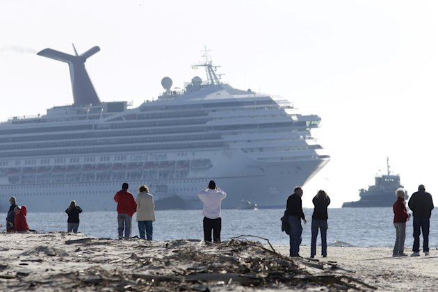 People on Spanish Fort watch as a disabled Carnival Lines cruise ship is towed to harbor off Mobile Bay, Ala., Thursday, Feb. 14, 2013. The ship with more than 4,200 passengers and crew members has be