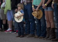 A young boy holds his hat as he and others stand for the national anthem before the start of the Prescott Frontier Days Rodeo, Wednesday, July 3, 2013 in Prescott, Ariz. A mile-high city about 90 miles northwest of Phoenix, Prescott remains a modern-day outpost of the pioneer spirit. It's that spirit that will guide officials as they navigate the days ahead and figure out how to honor the elite Hotshot firefighters who died in a nearby wind-driven wildfire that is still burning. (AP Photo/Julie Jacobson)