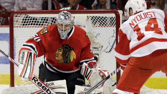 Chicago Blackhawks goalie Corey Crawford (50) blocks a shot by Detroit Red Wings' Gustav Nyquist (14) during the first period of Game 5 of the NHL hockey Stanley Cup playoffs Western Conference semifinals in Chicago, Saturday, May 25, 2013. (AP Photo/Nam Y. Huh)